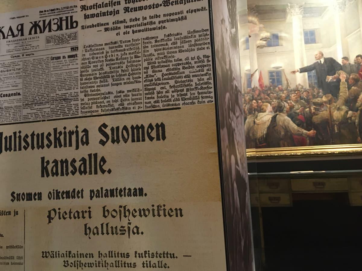 Vanhoja lehtileikkeitä Lenin-museon pylväässä. Taustalla maalaus, jossa Lenin puhuu kansalle.