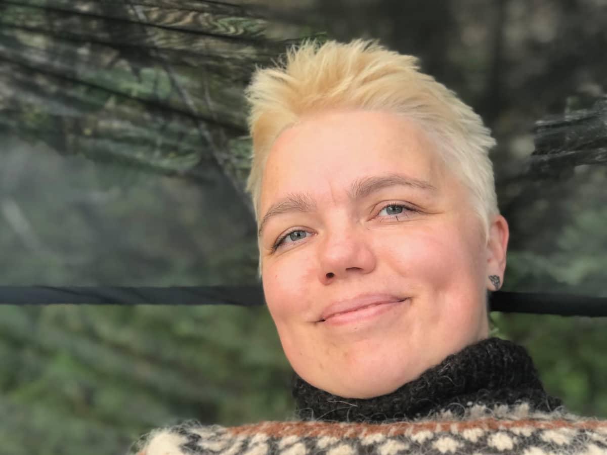 Kasvokuva naisesta joka istuu riippumatossa ja hymyilee kameralle
