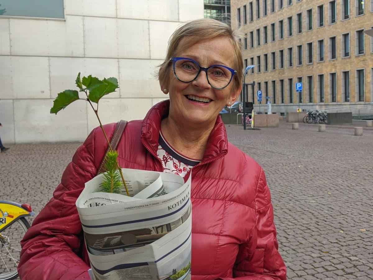 Anita Ventelä sylissään kuusen, männyn ja koivun taimet.