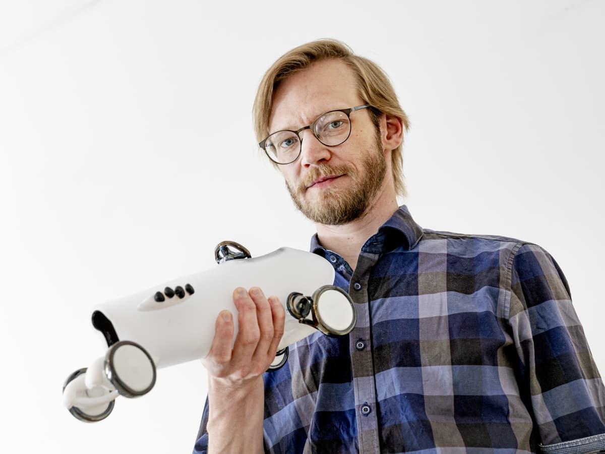 Lasinpuhaltaja Kaappo Lähdesmäki pitää kädessään tekemäänsä kilpa-auto taideteosta.