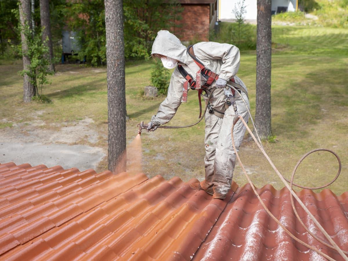 Maalari ruiskumaalaa omakotitalon kattoa.