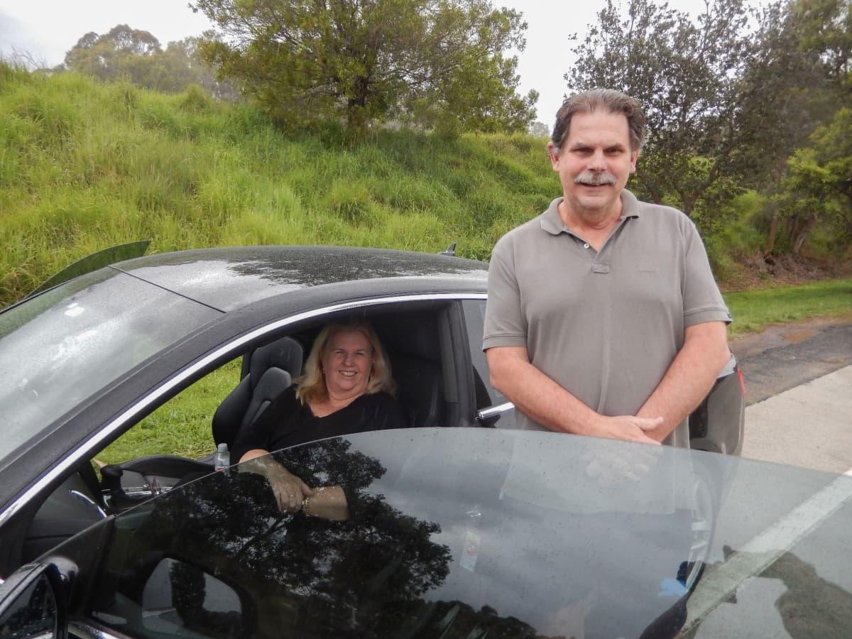 Nainen istuu autossa ja mies seisoo auton sivustalla.