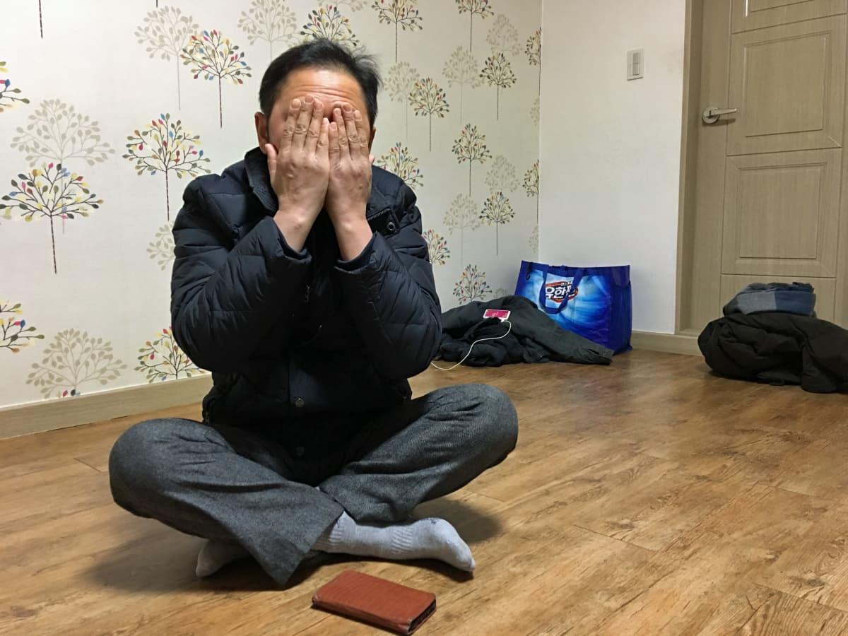 Pohjoiskorealainen Lee peittää kasvonsa käsillään.
