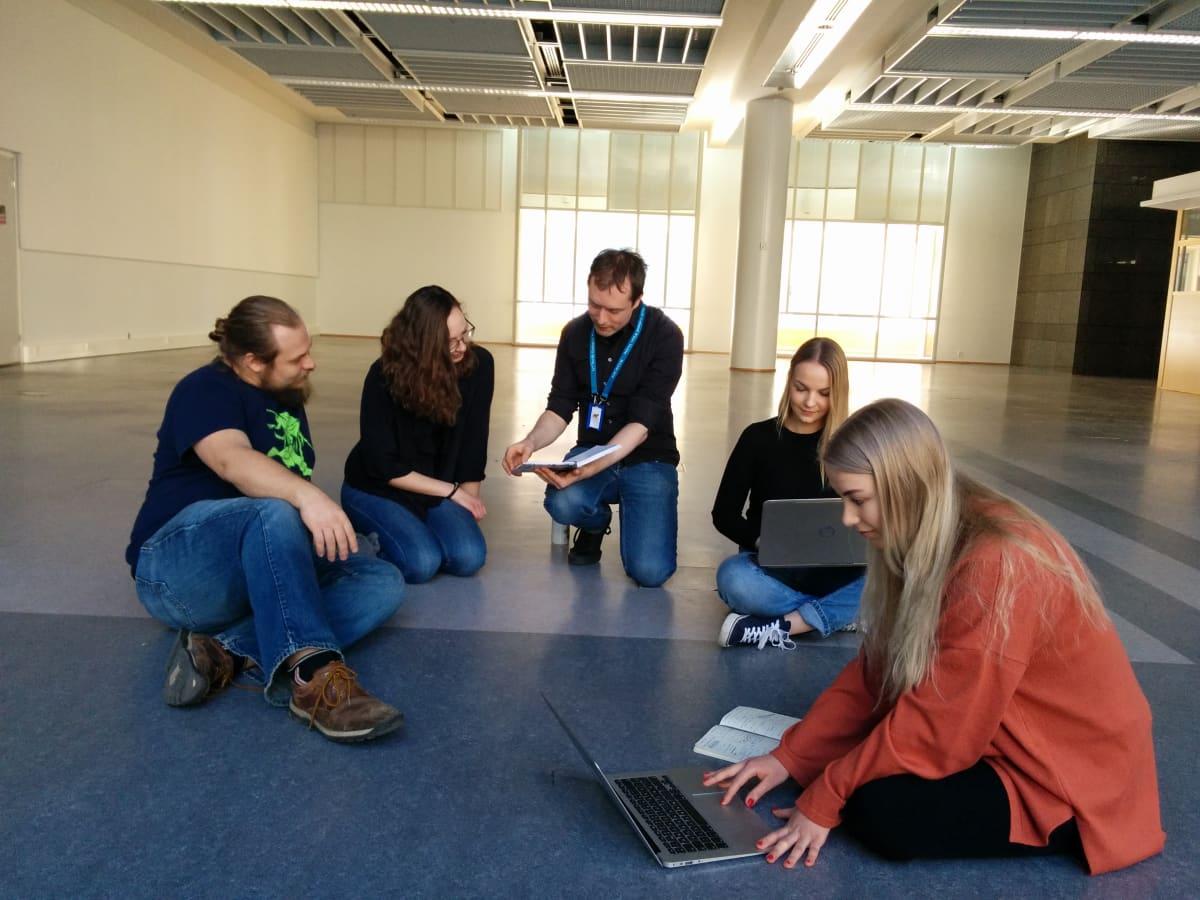 Opiskelijat istuvat tyhjillään olevan toimistosalin lattialla ideoimassa. Kahdella on kannettava tietokone. Yksi näyttää toiselle vihosta jotain.