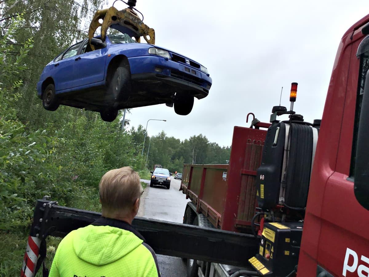 Hylättyä romuautoa kuljetetaan tienvarresta pois purkaamolle kierrätystä varten.