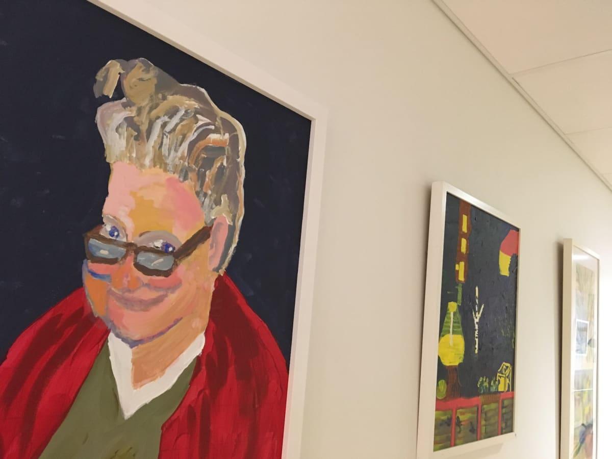 Kolme maalausta rivissä valkoisella seinällä. Etualalla maalaus silmälasipäisestä naisesta, joka on taiteilija Minna Ervanne itse.