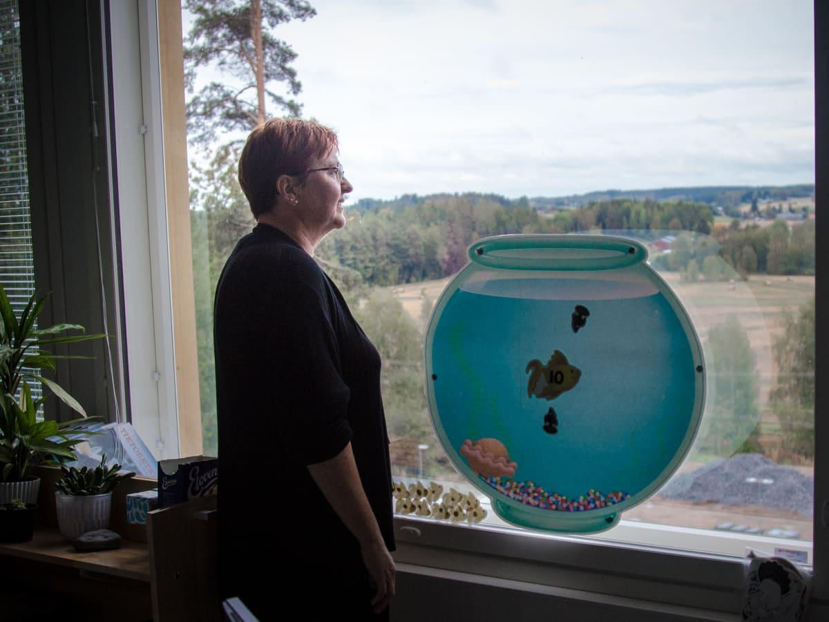 rehtori Annukka Alppi katsoo maisemia koulun ikkunasta