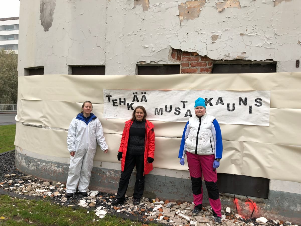 Suojellun funkkishuoltamon seinille maalataan kantaa ottavaa katutaidetta. Kuvassa ovat opiskelijat Teea Viherkari, Maria Talvensaari ja Johanna Piirainen.