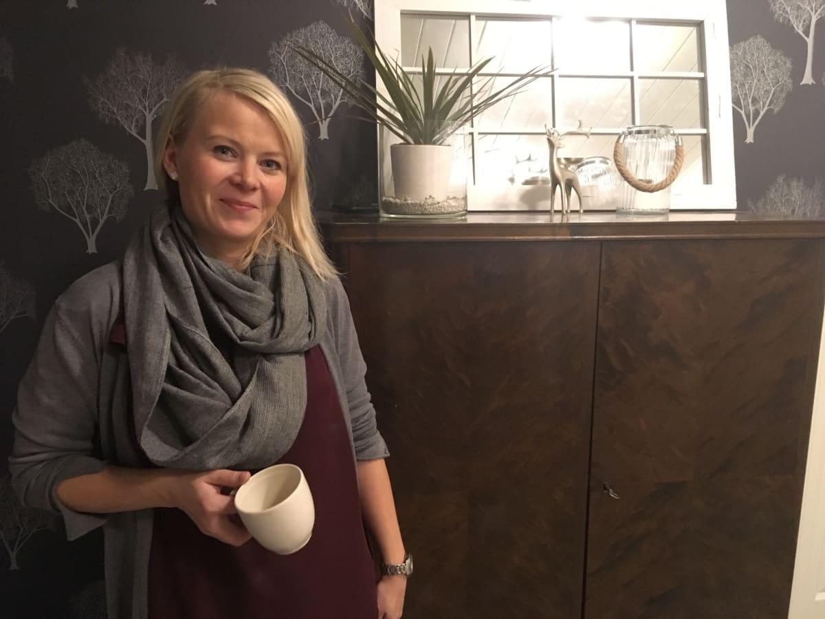 Any Rytkönen kotonaa kahvikuppi kädessä.