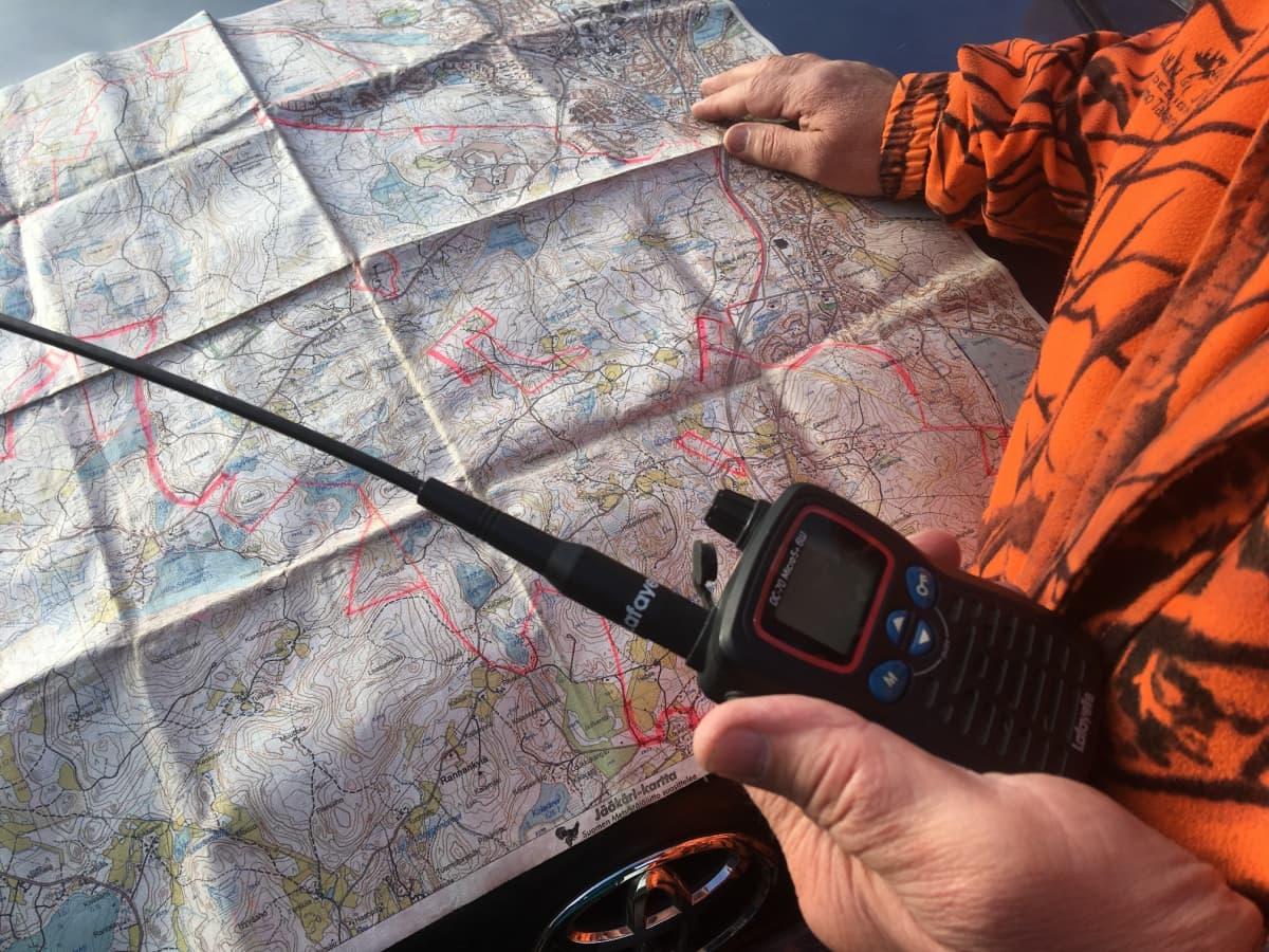 mies tutkii metsästysalueen karttaa auton konepellillä