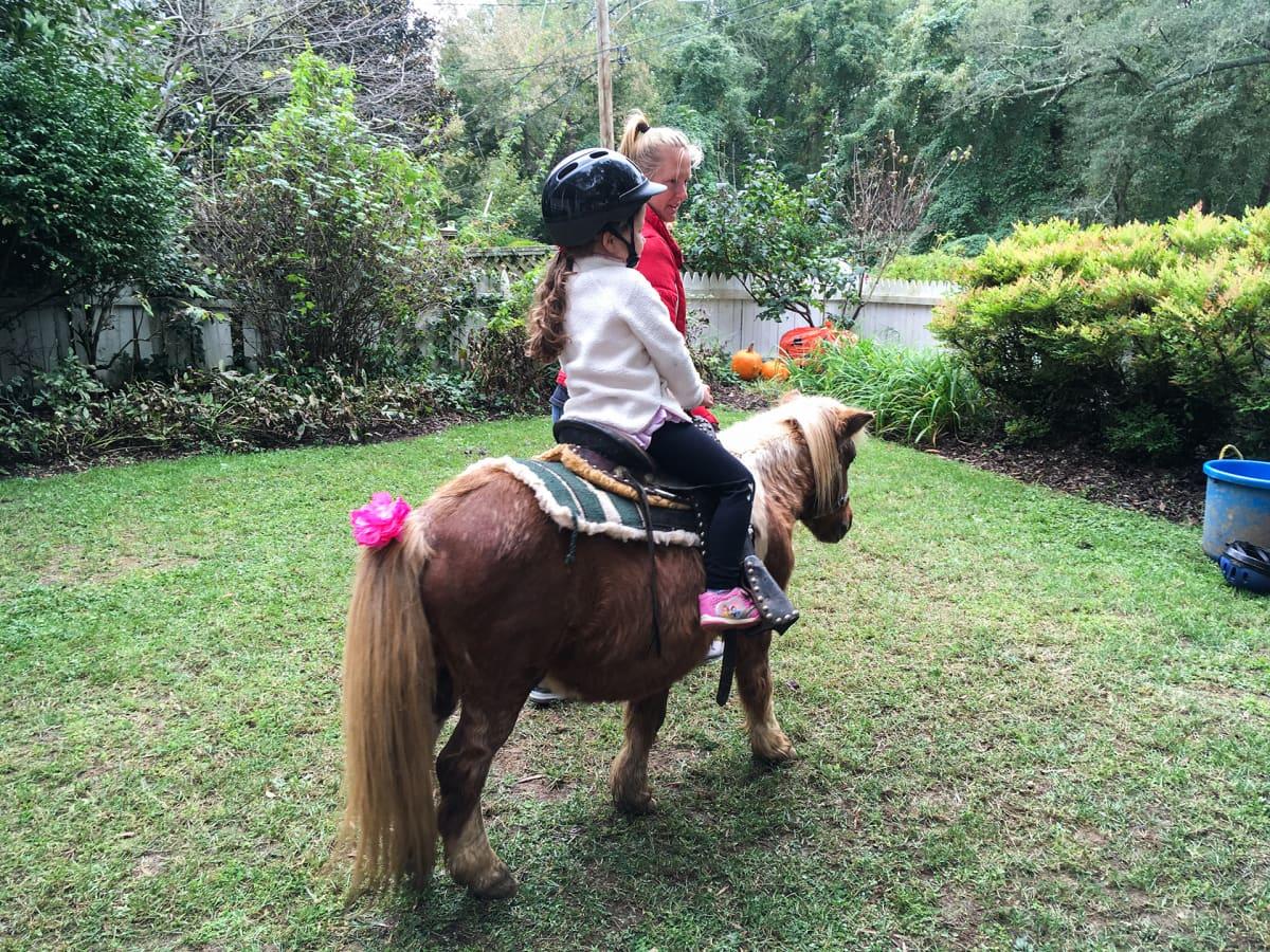 Lapsi ratsastaa ponilla.