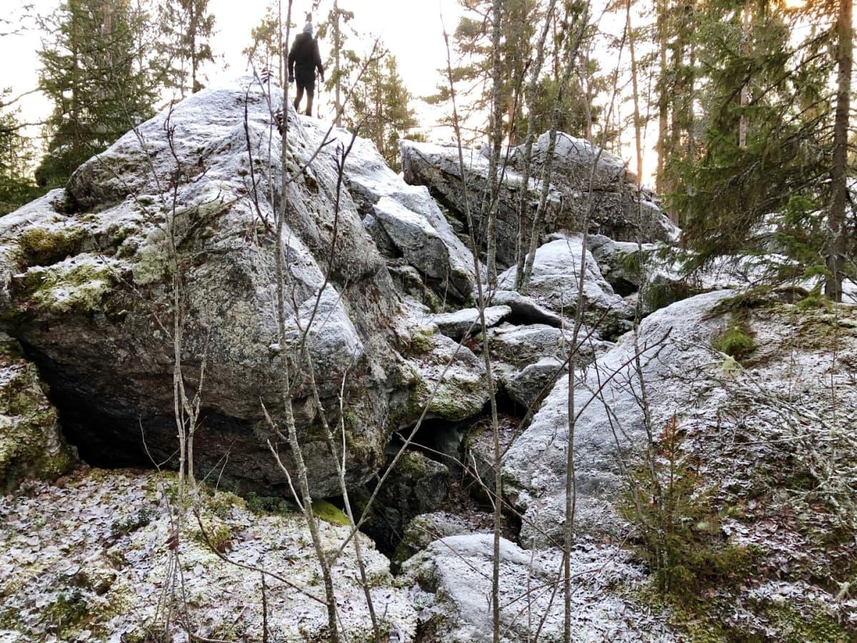 Retkeilijä suuren kivenlohkareen päällä