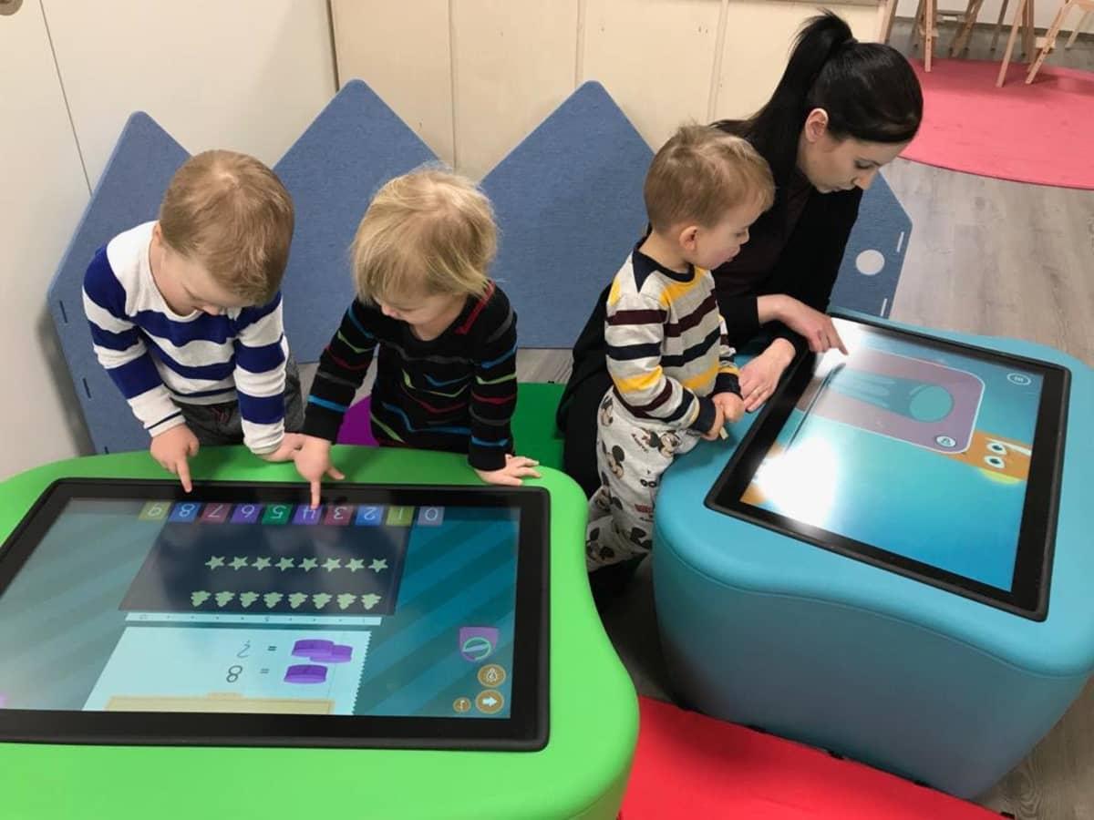 Lapset ja päiväkodin johtaja pöydän kokoisten tablet-tietokoneiden ääressä.