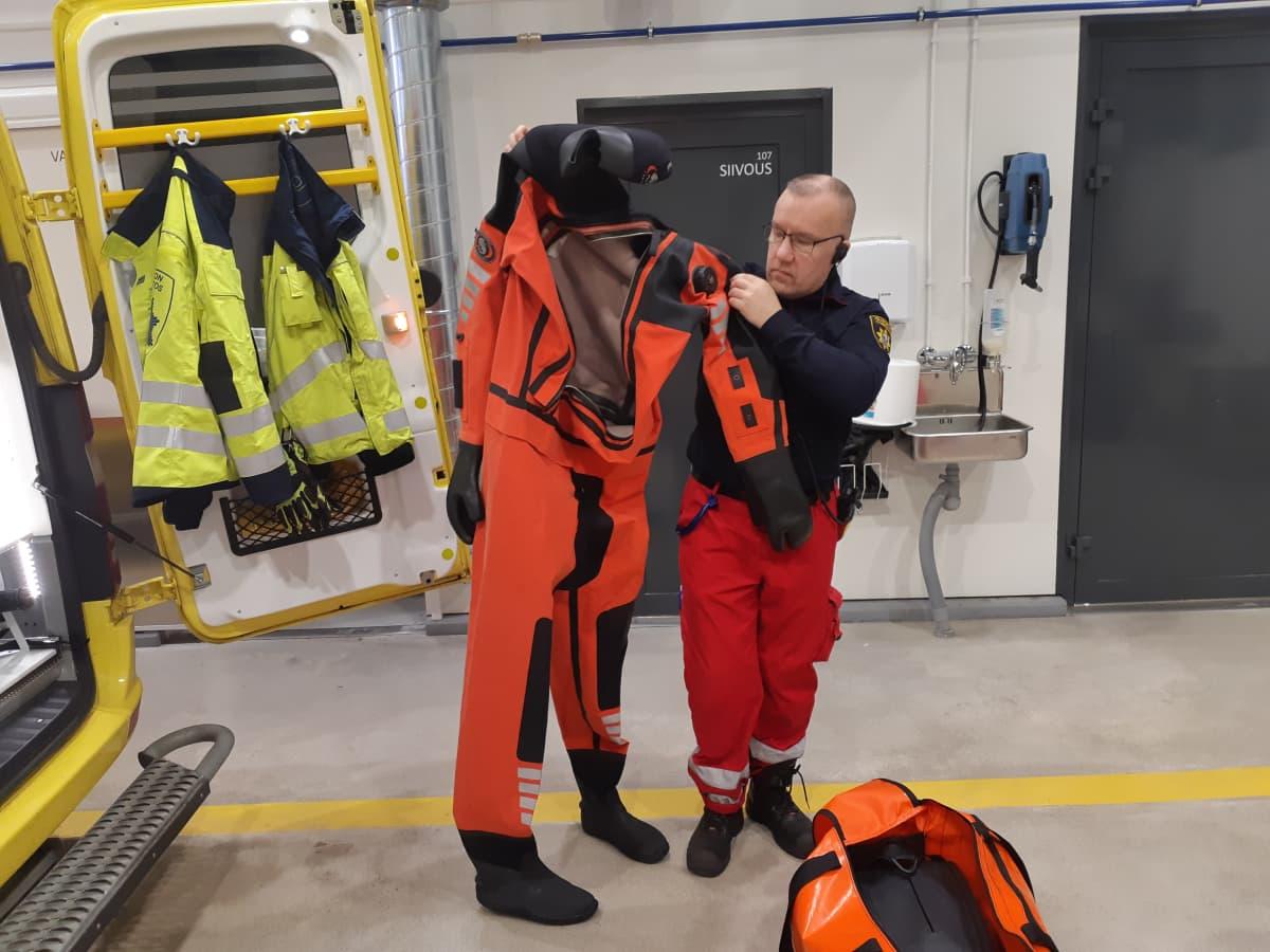 Pelastushenkilö Mika Hanska esittelee pintapelastuksessa käytettävää kuivapukua.