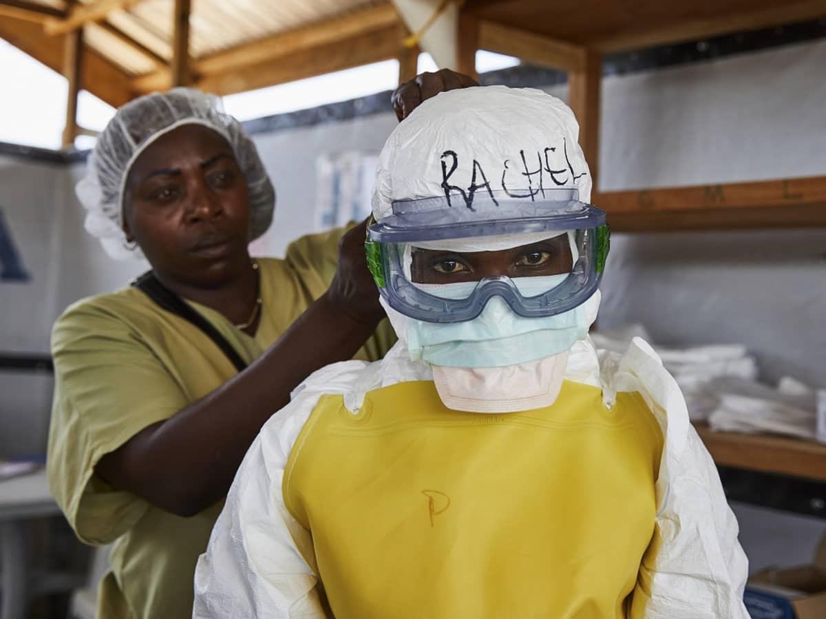 Kuvassa puetaan suojavarusteita hoitajan päälle Benin kaupungissa.