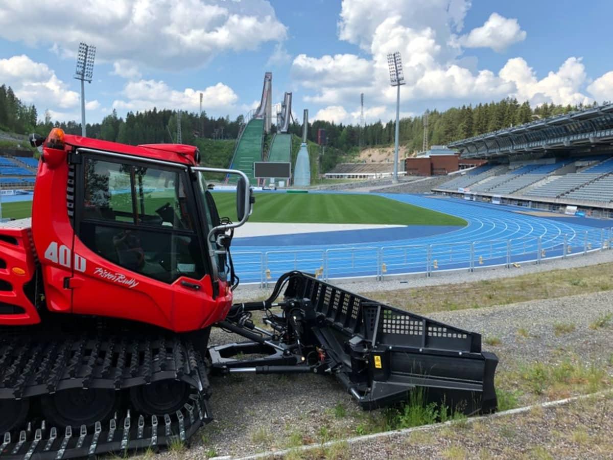 Pysäköity latukone seisoo kesäisen stadionin reunalla.