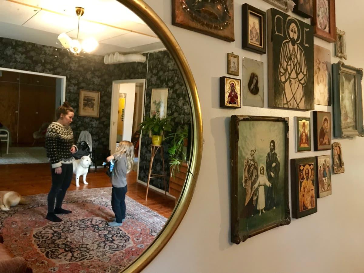 Ikoneja olohuoneen seinällä. Vieressä on pyöreä peili, josta kuvastuu nainen, lapsi ja kaksi koiraa.