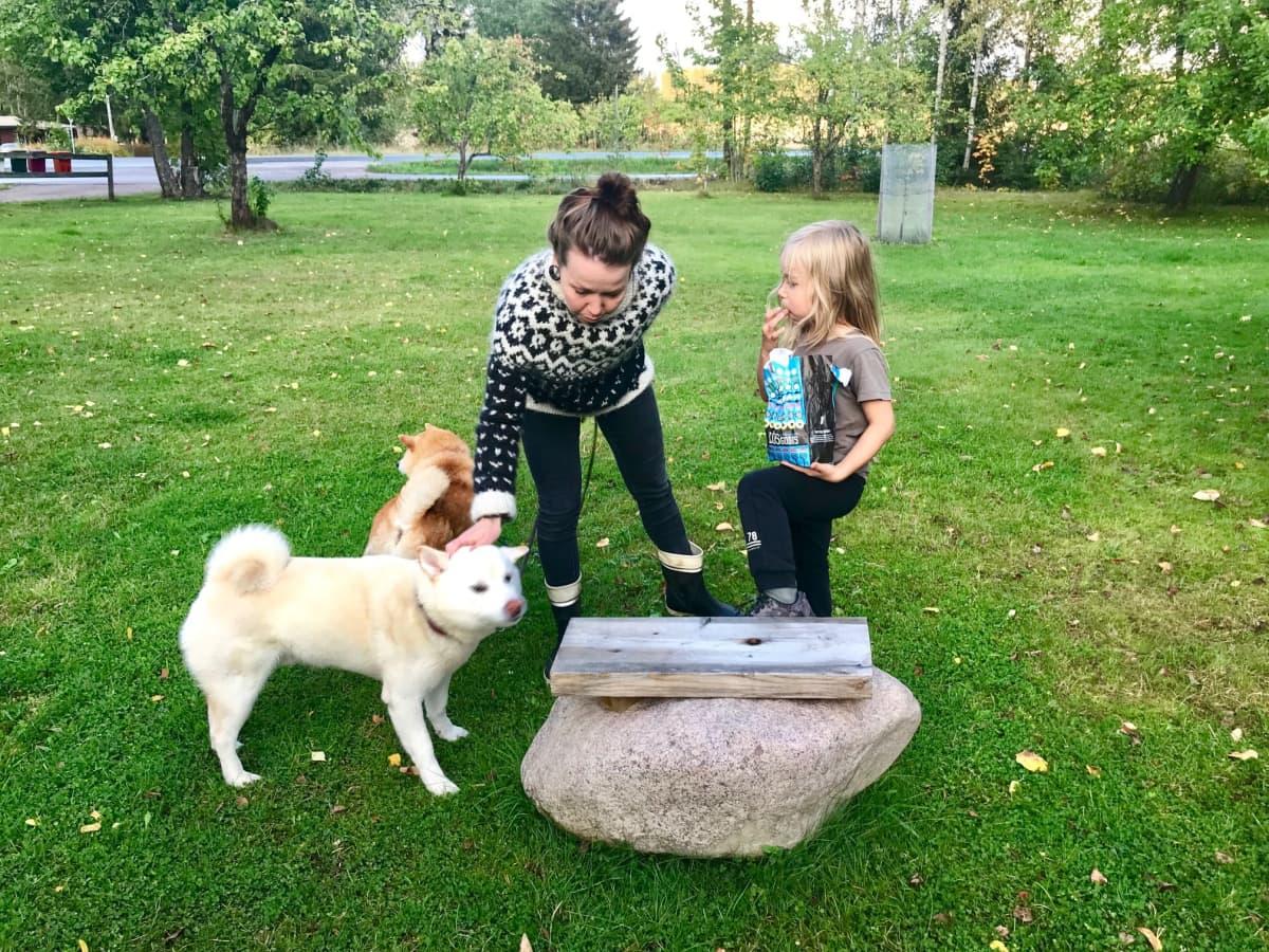Kaksi koiraa, nuori nainen ja pieni lapsi ulkona vihreässä puutarhassa.