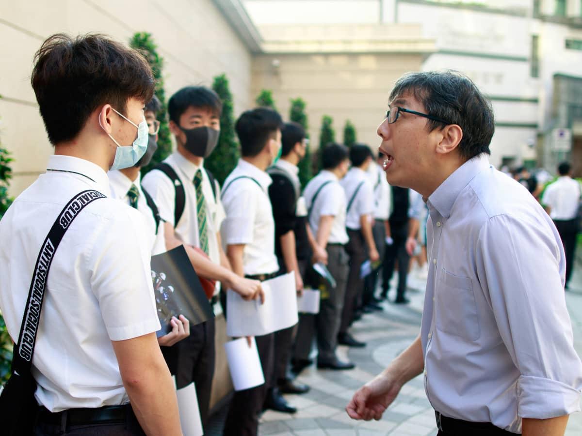 Opettaja läksyttää mielenosoitukseen osallistuvia oppilaita.