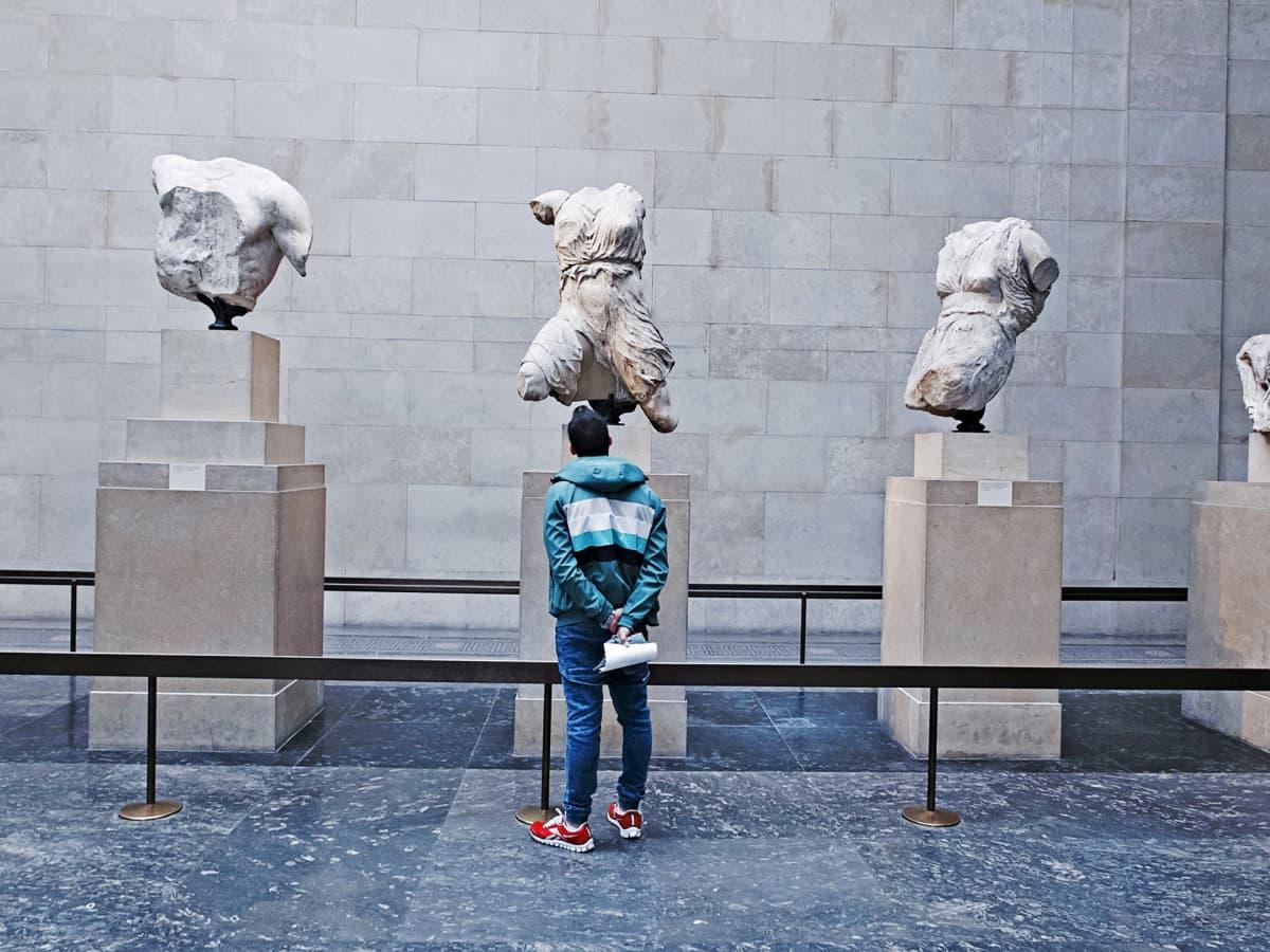 Turisti katselee Parthenon-temppelin veistoksia British Museumissa.