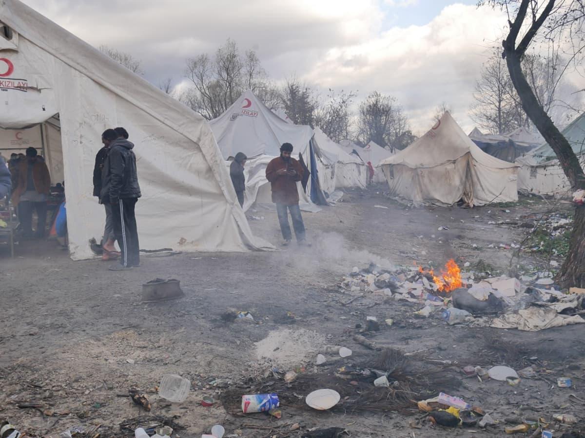 Kuvassa telttoja ja ihmisiä. Etualalla palaa nuotio.
