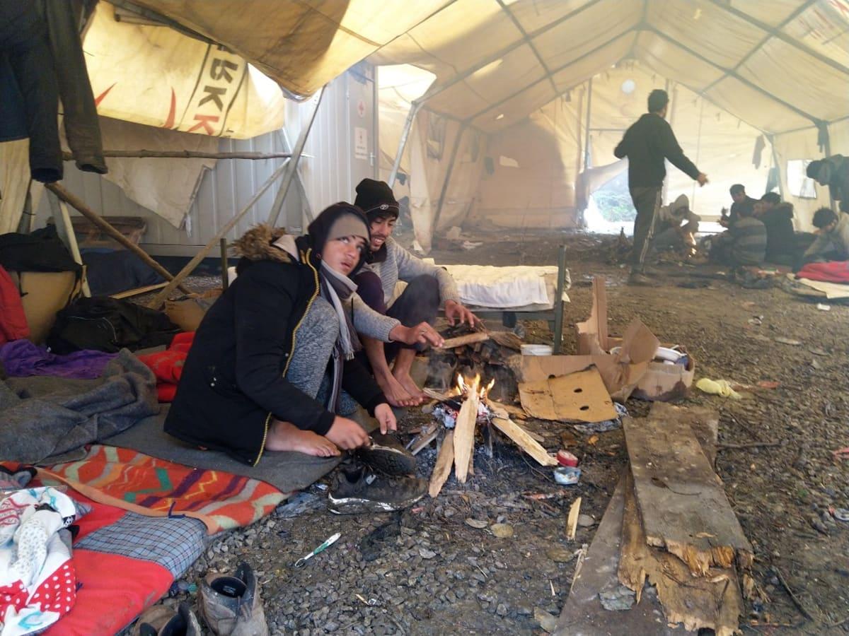 Etualalla kaksi miestä istuu telttaan sytytetyn nuotion ääressä.