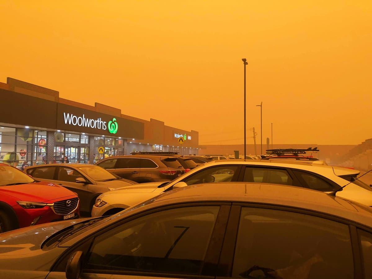 Keltaiseksi värjäytynt taivas supermarketin parkkipaikan taustalla.