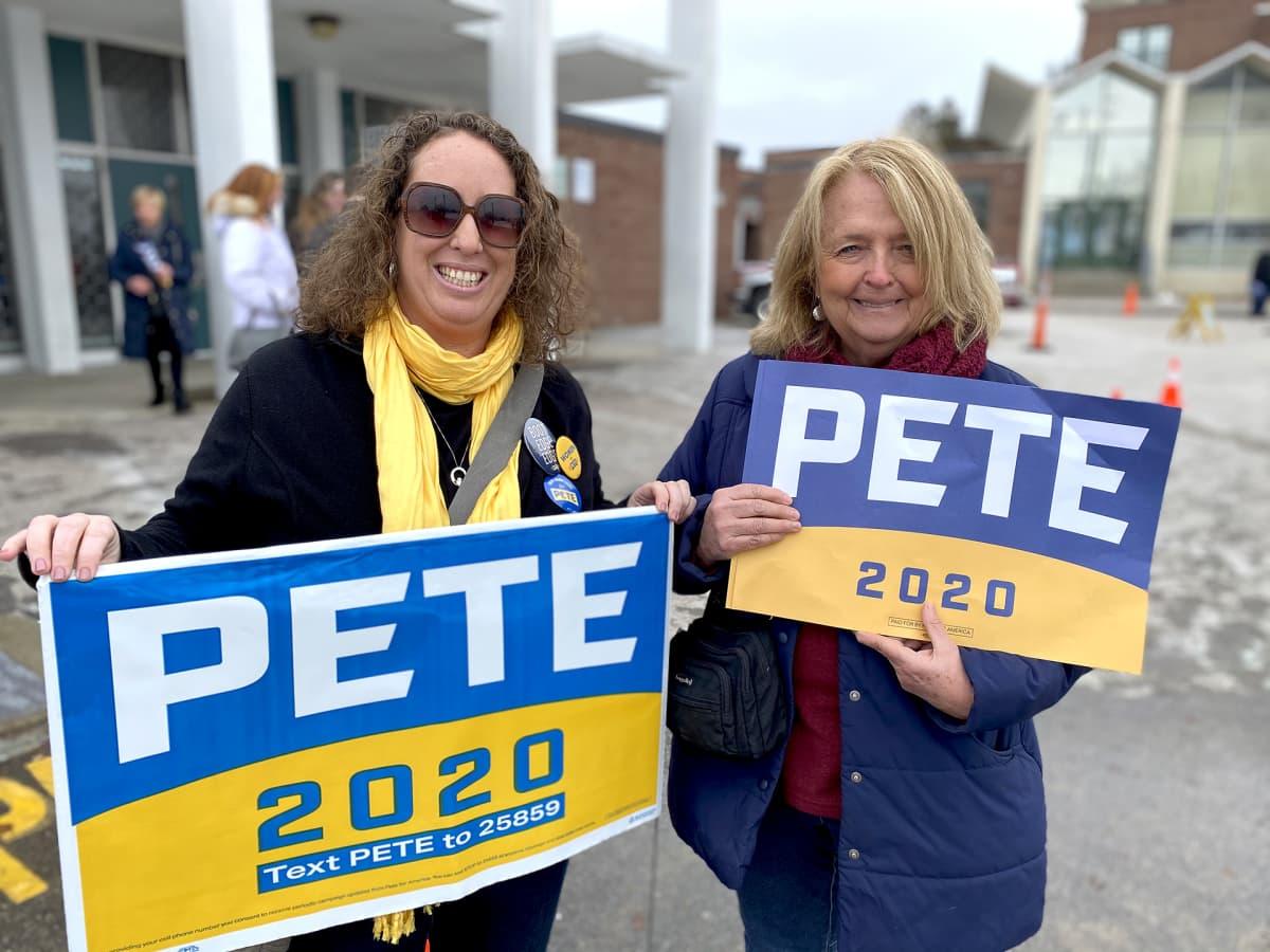 Pete-kylttejä kantavat rouvat.