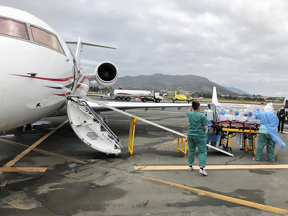 Sairaanhoitajat siirtävät potilasta lentokoneesta.