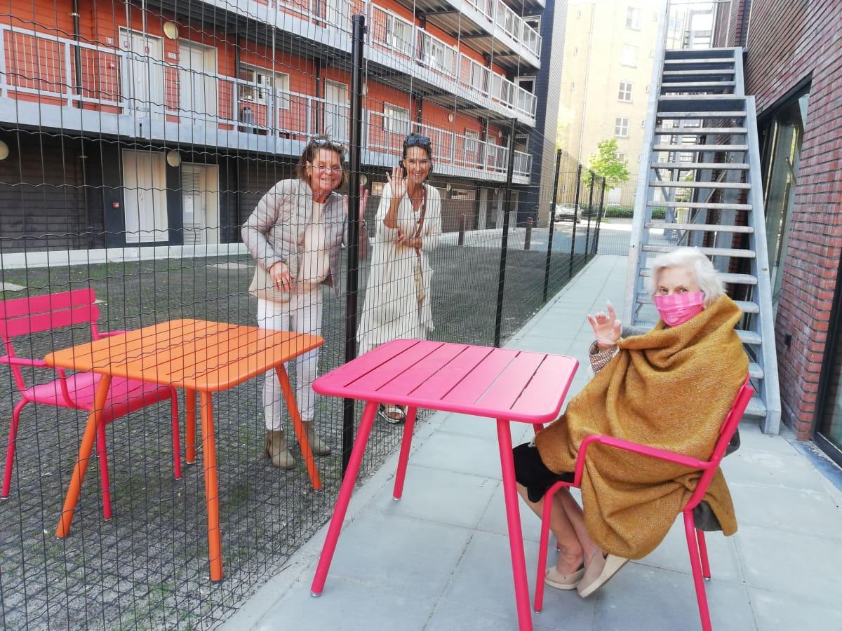 Omaiset vierailevat belgialaisessa hoivakodissa aidan takana.