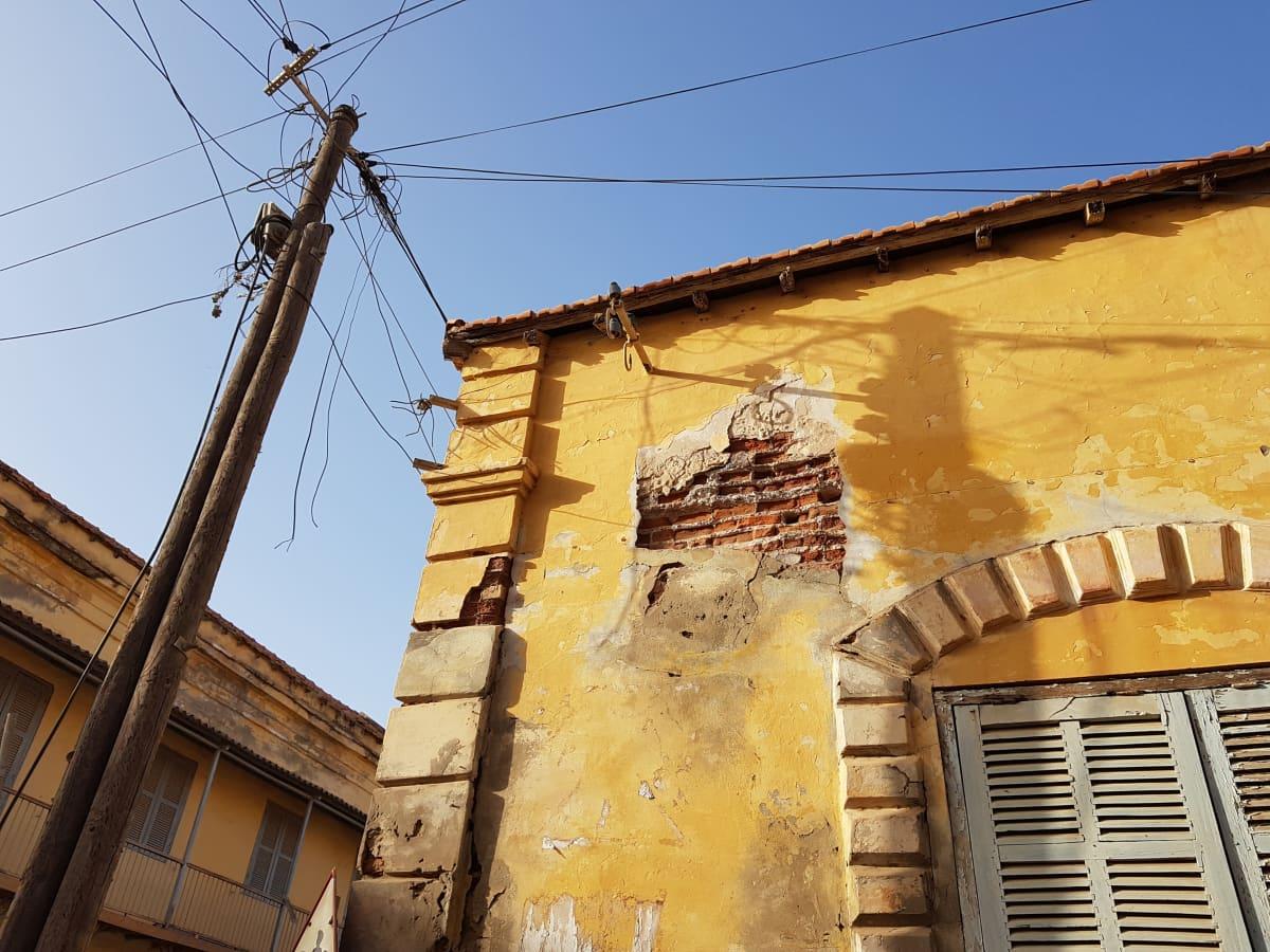 Vanhan talon seinä ja tolppa, jossa on paljon sähköjohtoja.