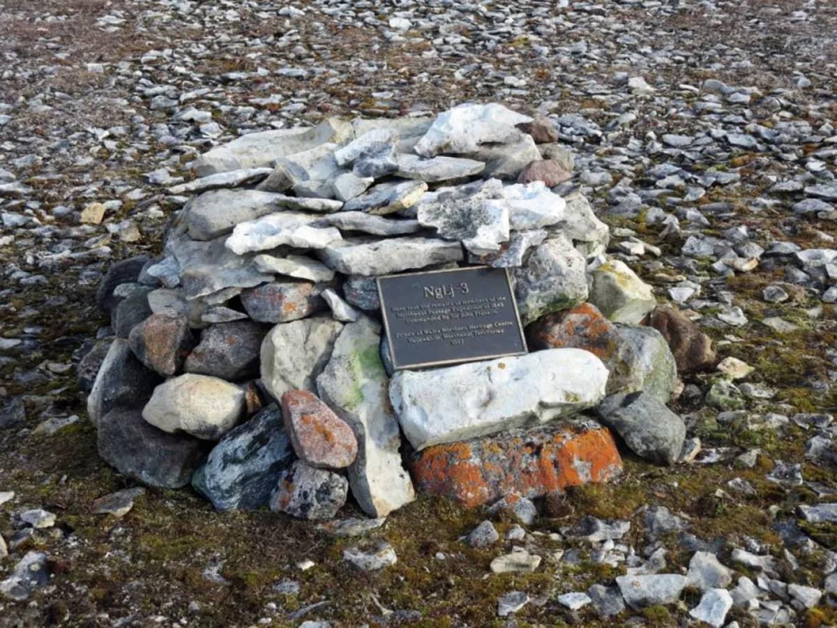 Kivistä kasattu muistomerkki, jonka kyljessä on metallilaatta.