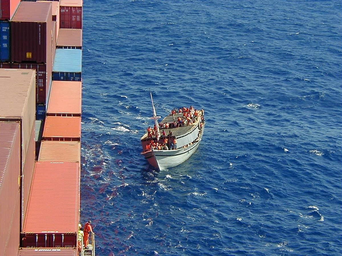 Pakolaisvene merellä rahtilaivan vierellä.