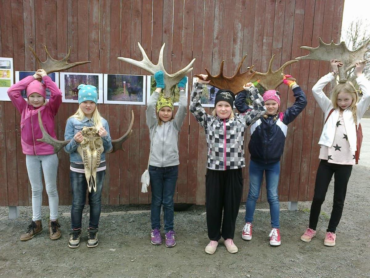 Kiteeläisen koulun kolmasluokkalaisia tyttöjä, jotka pitelevät hirven sarvia päidensä päällä.