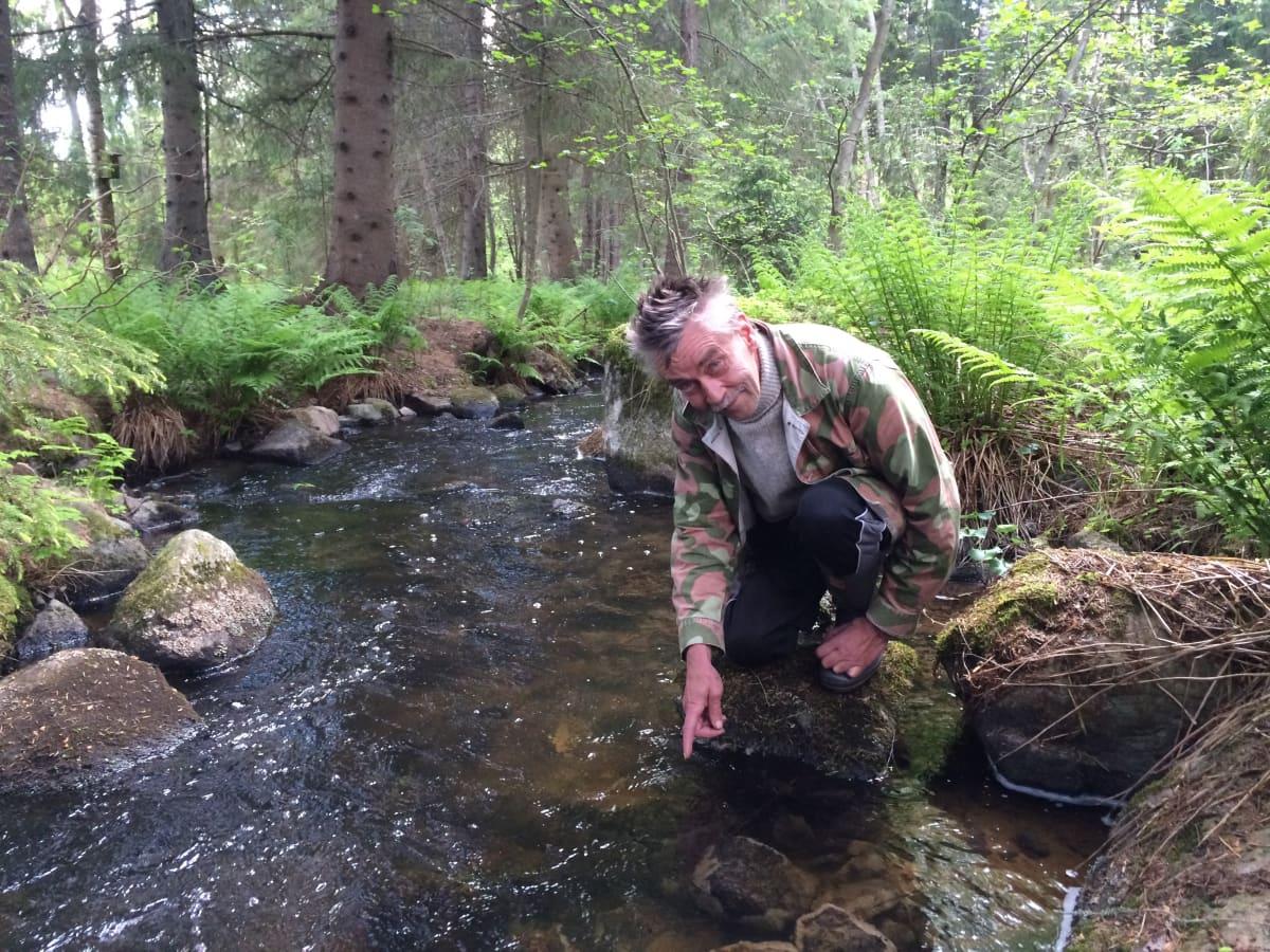 Mies kyykyssä puron äärellä.