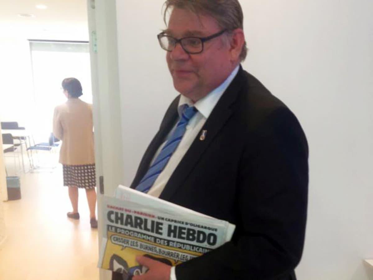 Timo Soini Brysselissä Charlie Hebdo-lehti kädessään.