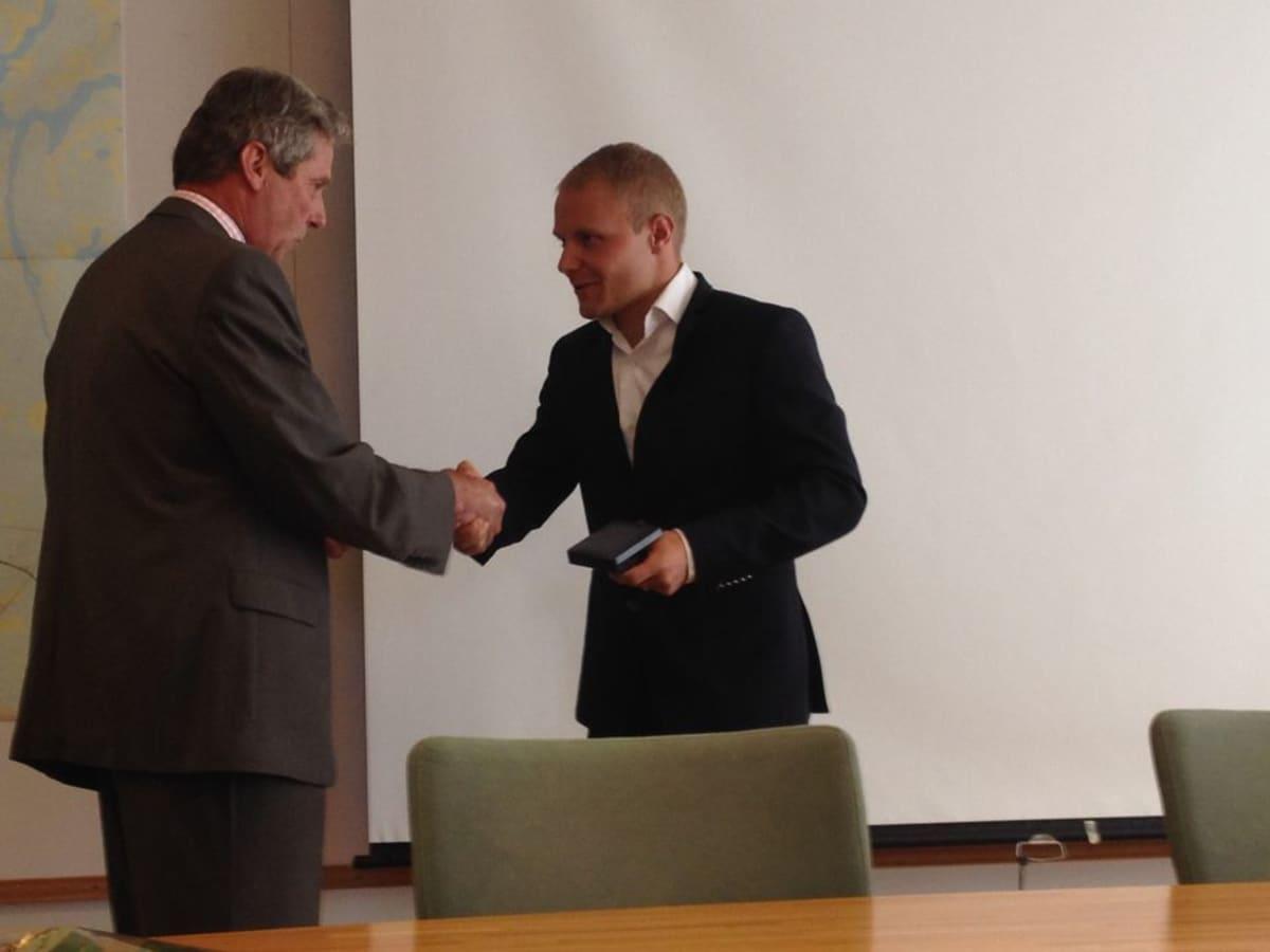 Kunnanjohtaja luovuttaa Valtteri Bottakselle Nastola-mitalin.