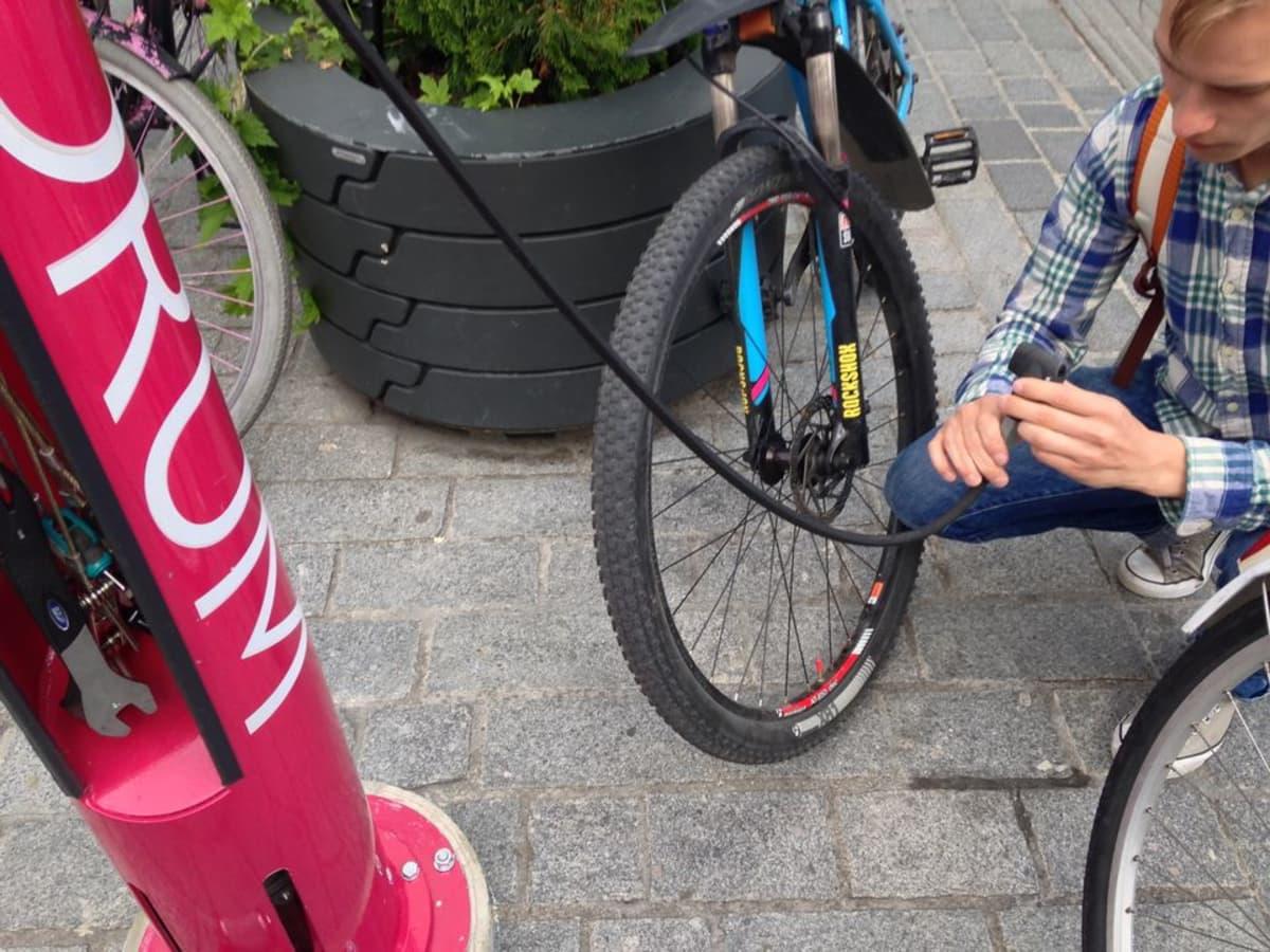 Nuori mies täyttää pyörän rengasta.