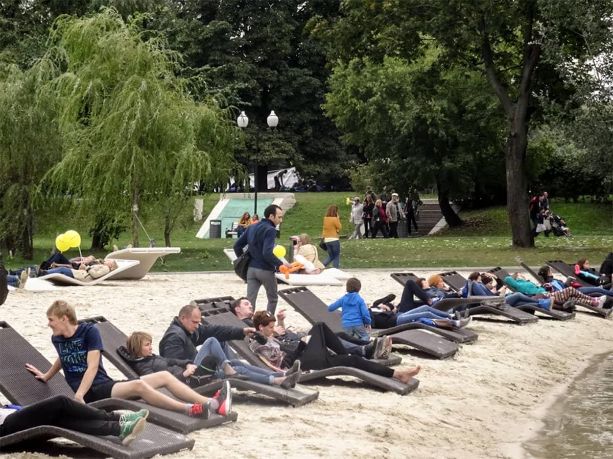ihmisiä lepotuoleissa puistossa