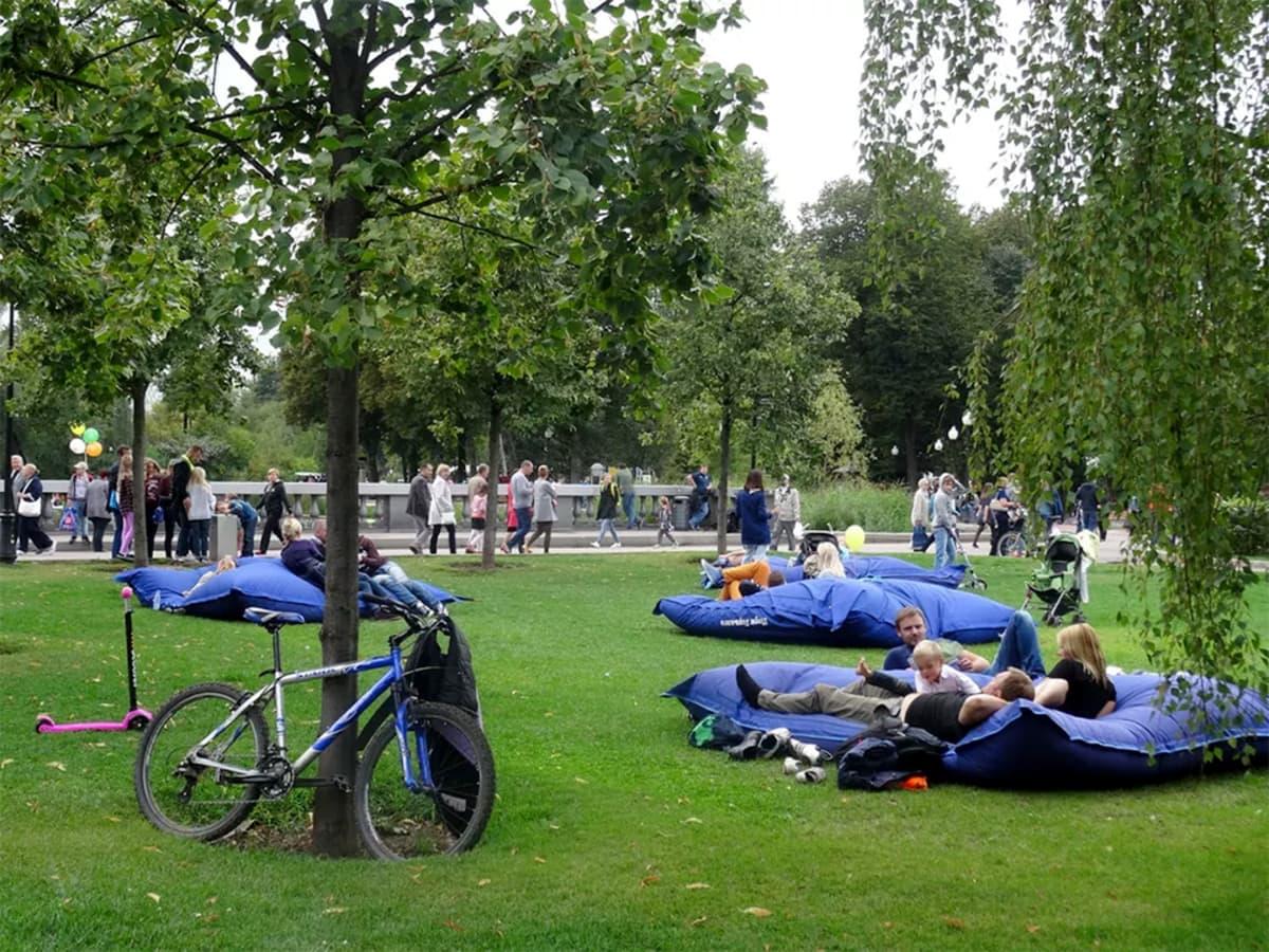 ihmisiä loikoilee nurmikoilla olevilla tyynyillä