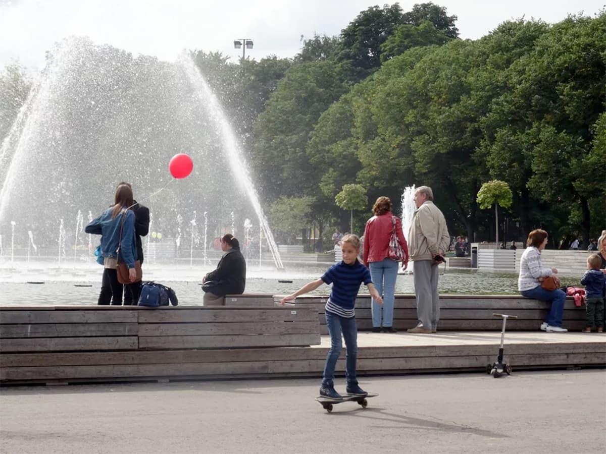 suihkulähde puistossa ja rullalautaileva tyttö