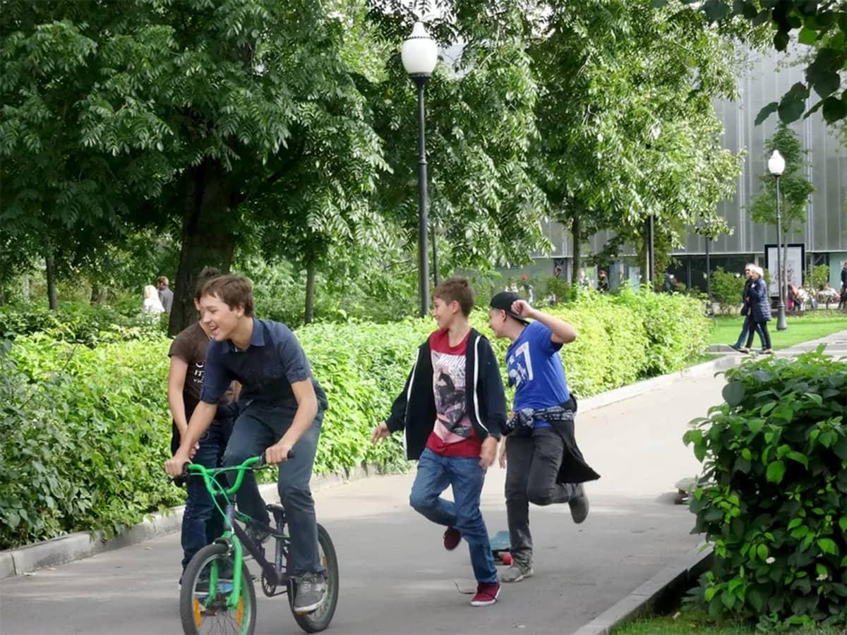 puistossa juoksevia poikia, yksi pyöräilee