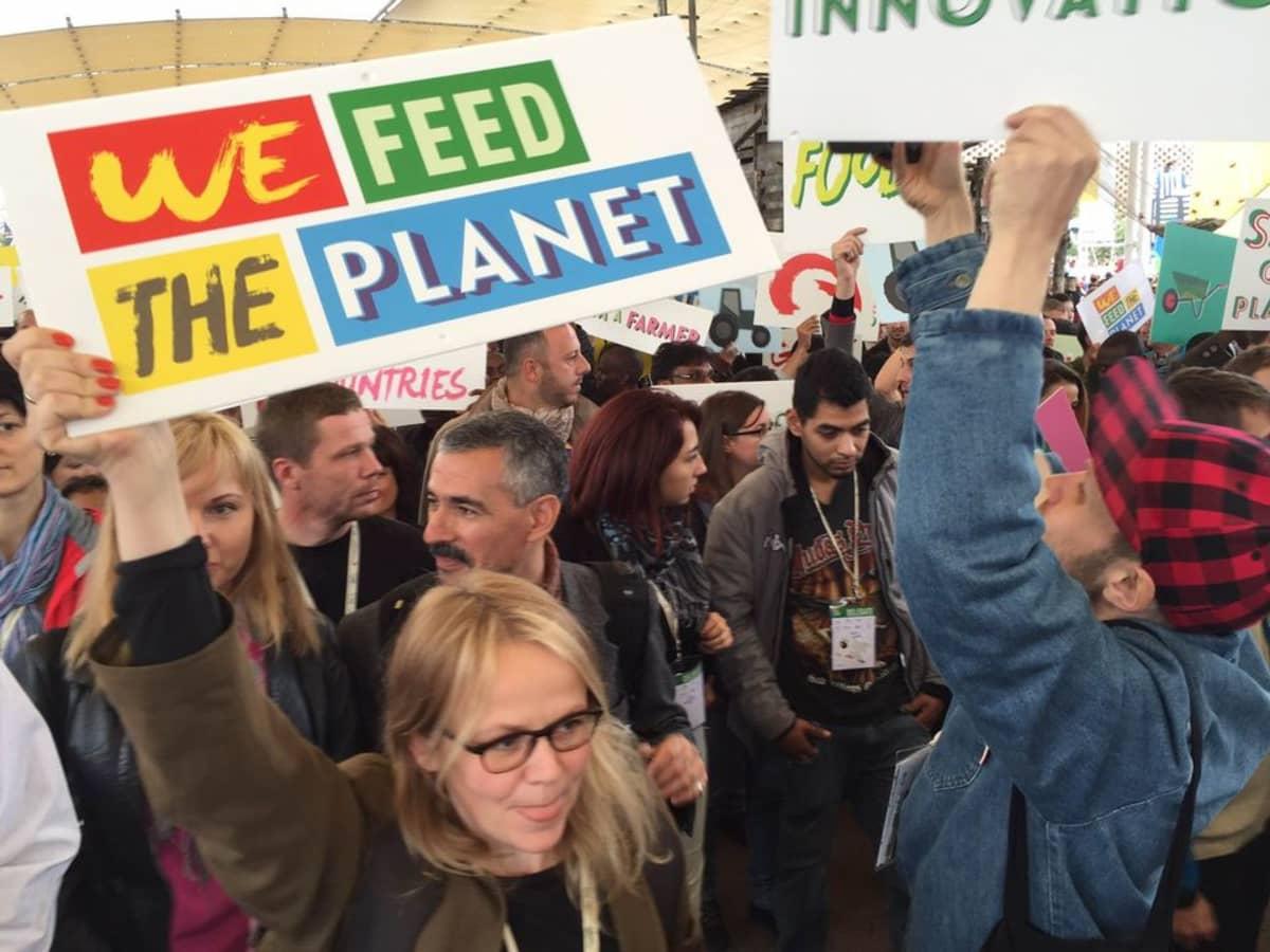 """Mielenosoittaja pitelee kylttiä, jossa lukee """"We Feed the Planet""""."""