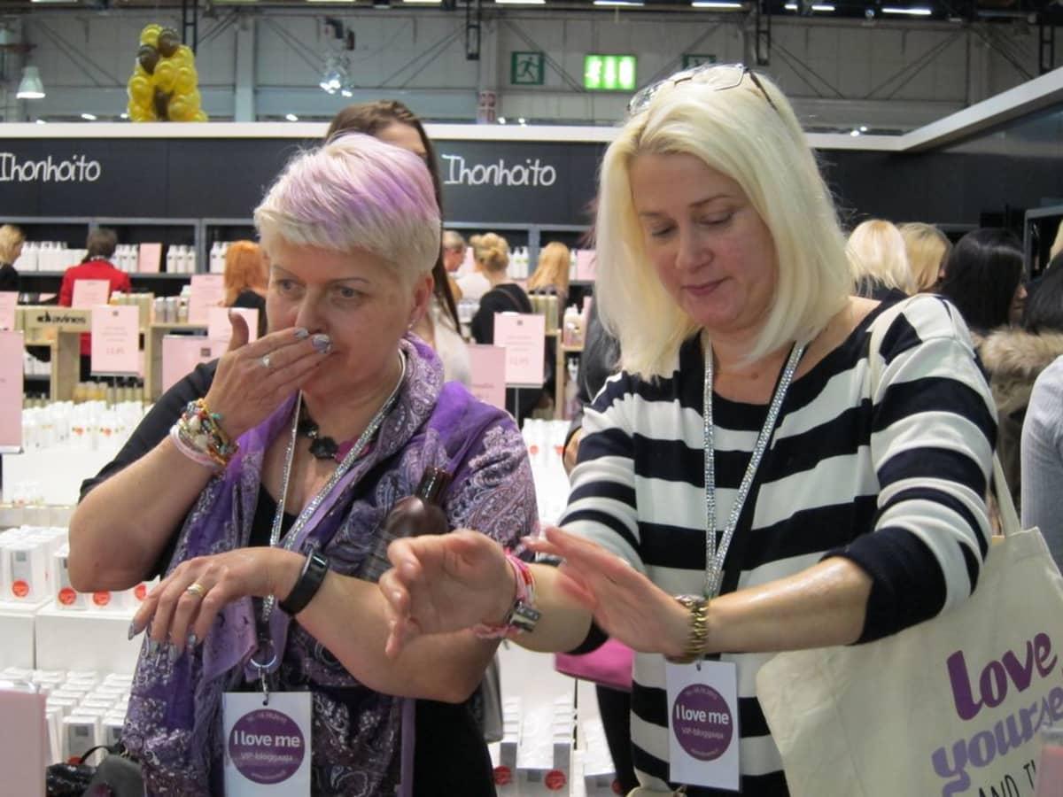 Kaksi keski-ikäistä naisbloggaajaa I love me -messuilla kokeilemassa ihotuotteita.