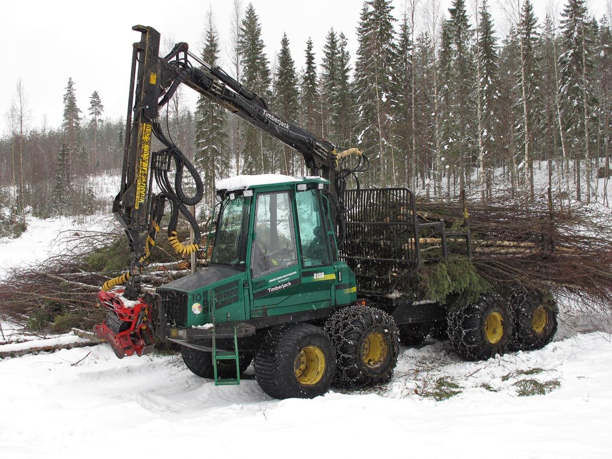 Vihreän värinen Timberjack-metsäkone kerää hakepuuta.