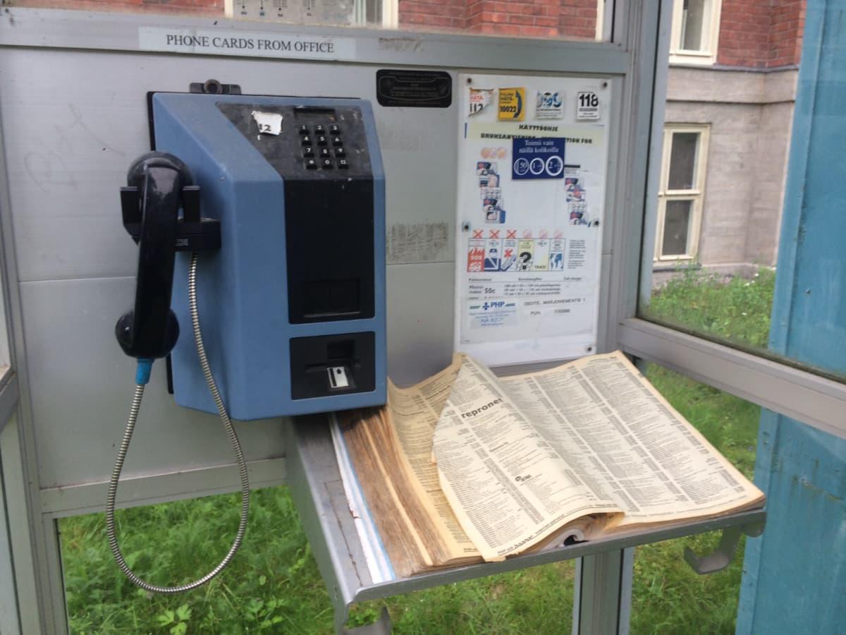 Puhelinkoppi  jossa on puhelin ja luettelo