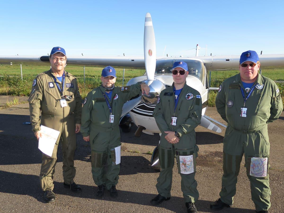 Neljä haalareihin pukeutunutta miestä lentokoneen edessä
