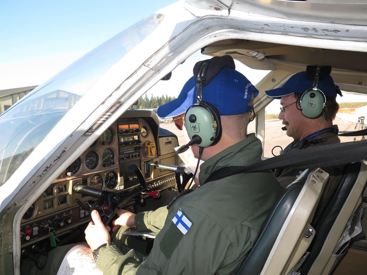 Kaksi miestä lentokoneen ohjaamossa valmiina lähtöön.