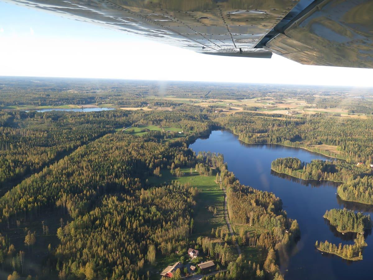 Järvi- ja metsämaisemaa ilmasta kuvattuna, ylälaidassa lentokoneen siipi.