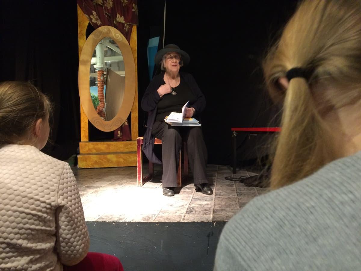 Kirjailija Kirsi Kunnas lukee runojaan kuvan etualalla oleville lapsille.